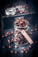 Coffee beans and vintage watch on a chain on a wooden background