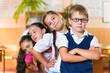 Four adorable schoolchildren standing in classroom