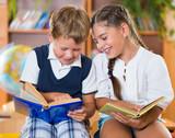 Two happy schoolchildren have fun in classroom - Fine Art prints