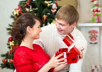 Young couple with gifts in front of Christmas tree  at home