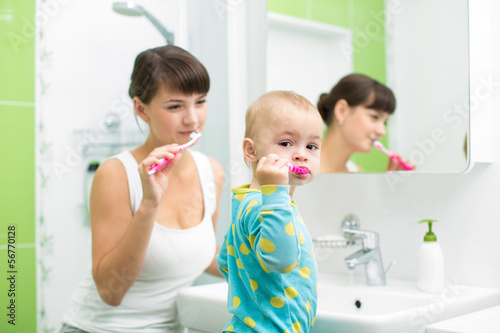 mother with baby brushing teeth