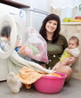 mother with little baby doing laundry