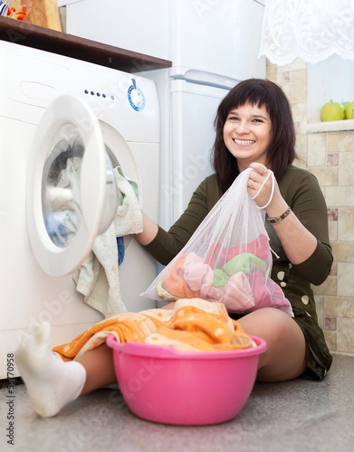 Happy housewife with laundry bag