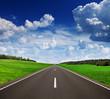 Asphalt road in green fields under beautiful sky