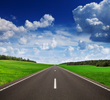Fototapety Asphalt road in green fields under beautiful sky