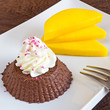 creamy chocolate chia pudding on a plate with sliced mango