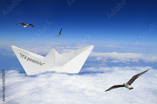 Origami boat floating in clouds