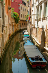 Colorful buildings and boats in Venice canal passage