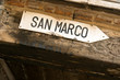 Directional sign to San Marco square on old Venetian building