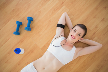 Amused fit brown haired model in sportswear listening to music