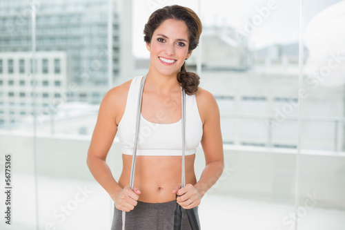 Sporty smiling brunette holding skipping rope