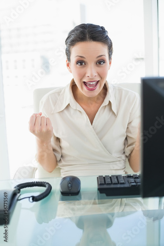 Joyful stylish brunette businesswoman raising her fists