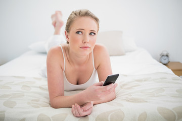 Natural pensive blonde lying on bed and using smartphone