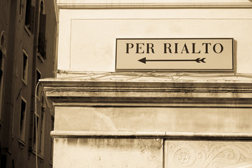 Directional sign to Rialto bridge on old Venetian building