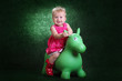 little girl on a green toy pony