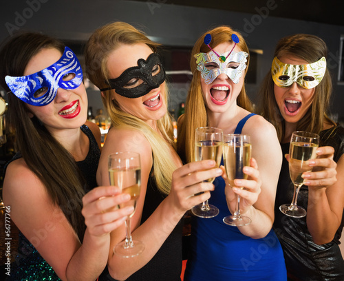 Attractive friends with masks on holding champagne glasses
