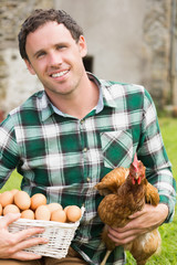 Young man holding his chicken and basket of eggs