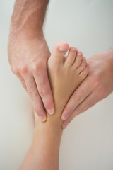 Close up of physiotherapist kneading patients foot