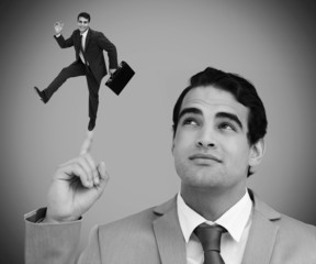 Thoughtful businessman showing shrunk colleague dancing on his f
