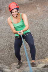 Smiling girl abseiling down rock face