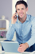 Smiling casual man holding tablet and phoning