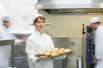 Cute female baker holding a baking tray with rolls on it