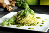 pasta vegetariana spaghetti con pesto sfondo verde