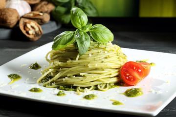 pasta vegetariana spaghetti con pesto sfondo grigio
