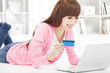 young woman online shopping at home with credit card