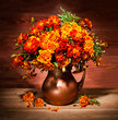 Still life with autumn flowers on a table in a copper vase