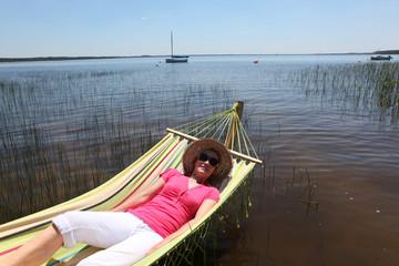 Woman in hammock by lake