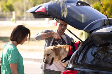 Giovane coppia che porta a fare passeggiata il loro cane