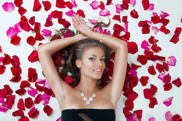 Beautiful woman lying on the petals of roses