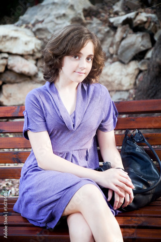 Sunset portrait of a girl on a bench