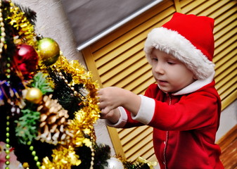 the boy decorates a New Year Christmas tree