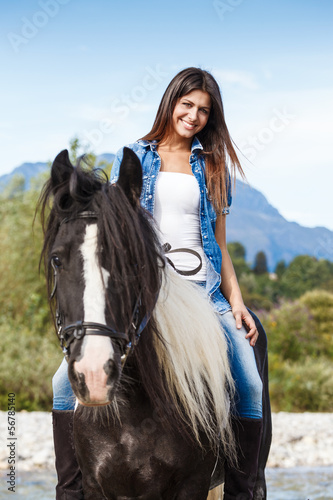 Young girl sitting on horse while crossing river in a mountainou