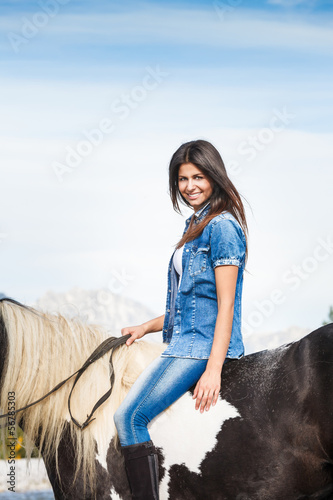 Smiling Young girl sitting on horse against blue sky