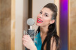 Girl with beautiful eyes and red lips in room with microphone
