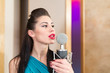 Beautiful woman with red lips in room with microphone