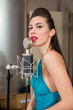 Beautiful girl with red lips sing in room with microphone