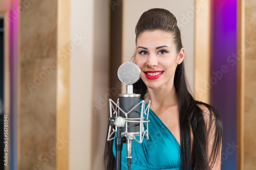 Smiling girl with red lips in room with microphone in Studio
