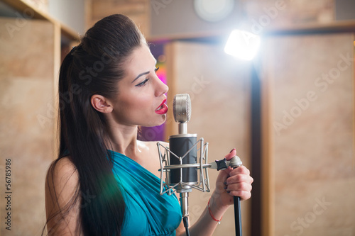 Beautiful girl with red lips holding a microphone and singing