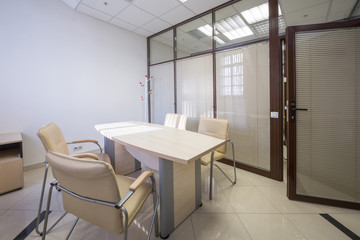 Meeting room blinds closed with a table and  chairs