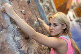Girl with concentrated face with climbing equipment hanging