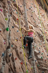 Young smiling girl engaged in climbing