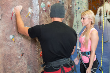 girl listens to instructions on climbing by coach