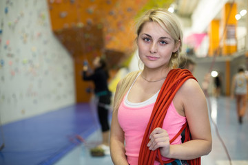 portrait of beautiful girl with rope on shoulder on climbing gym