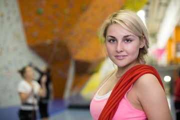 portrait of smiling girl with rope on shoulder on climbing gym