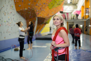 The girl with rope on shoulder on the climbing gym