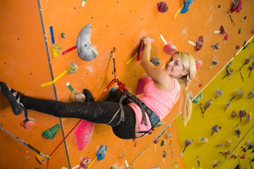 young smiling girl climbs steep wall on climbing gym